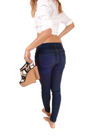 A closeup picture of a young woman from the back carrying her heels,in a white blouse and jeans, isolated on white background.