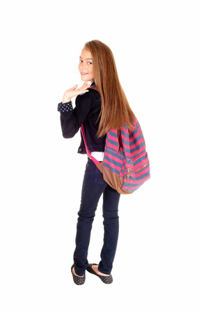 An eight year schoolgirl with her backpack over her shoulder standing forwhite background, waiving good by.