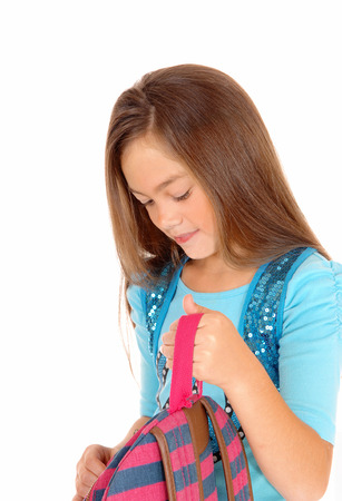 A pretty eight year old girl is looking in her backpack in a closeuppicture, isolated on white background. Imagens