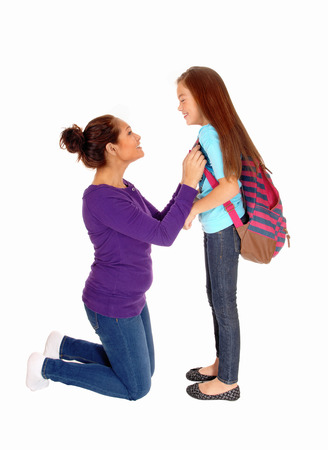 A mother kneeling before her daughter making her ready for school,isolated for white background. photo