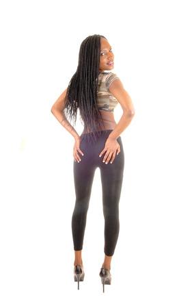 trenzas en el cabello: Un joven alto mujer afroamericana de pie desde la parte de atr�s, sosteniendo a su tope, con largo cabello trenzado negro, aislado en fondo blanco.