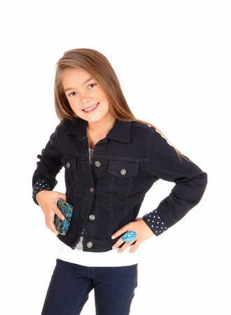 A pretty eight year old girl standing isolated for white background in jeans and a jean jacket, holding her purse. photo