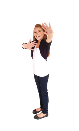 eight year old: A pretty eight year old girl holding her hand up smiling, and saying NO, isolated on white background. Stock Photo