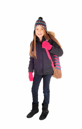 eight year old: A lovely eight year old girl with long blond hair, a hat and mittens with her backpack over her shoulder, isolated on white background.