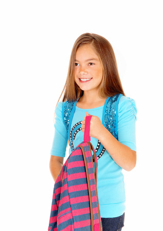 A pretty eight year old girl is looking and holding her backpack in a closeuppicture, isolated on white background.
