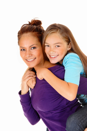 A mother and daughter playing for isolated white background, the girlsitting on the back of her mother in a closeup picture. photo