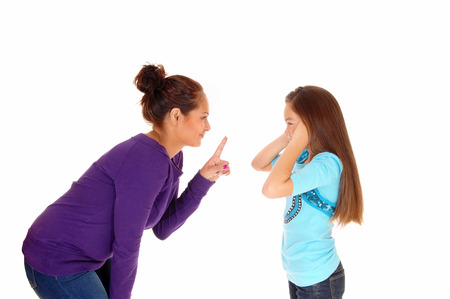 A mother is disciplining her young daughter and the girl holding herears closed, isolated for white background. Stock Photo
