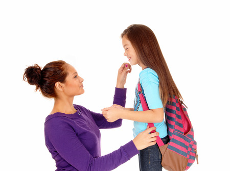 A mother getting her eight year old girl ready for school, the girl with abackpack, isolated on white background.
