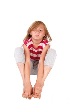 Een jonge acht jaar oud meisje zitten op de vloer, op zoek naar heel gek, zittend op de vloer, geïsoleerde voor witte achtergrond.