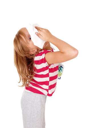 running nose: A lovely young blond girl holding a tissue on her running nose, blowing,isolated for white background.