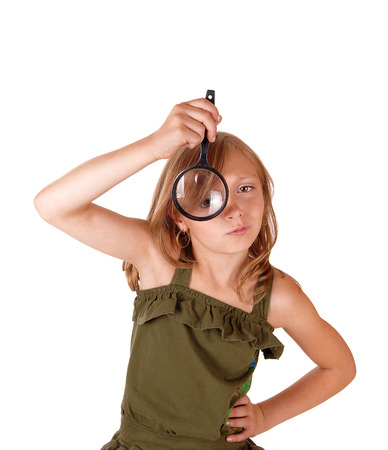eight year old: A eight year old girl holding a magnifying glass before her eye, isolatedfor white background.