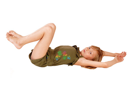 A pretty little girl in a olive green jumpsuit lying on her back on the floor,isolated over white background.