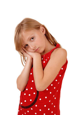 A lovely young girl holding her hands on her face, looking sad, isolatedon white background. photo