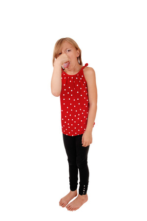 A young eight year old girl standing for white background, holding hernose for the bad smell and with her tongue out.