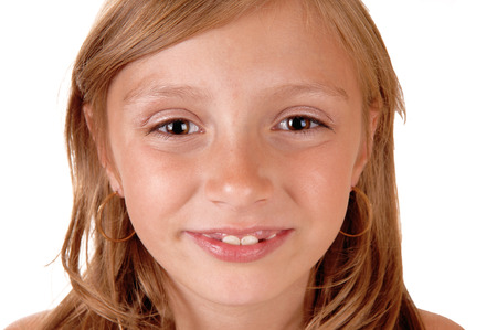 eight year old: A closeup picture of the face of a eight year old girl, smiling, isolatedfor white background. Stock Photo