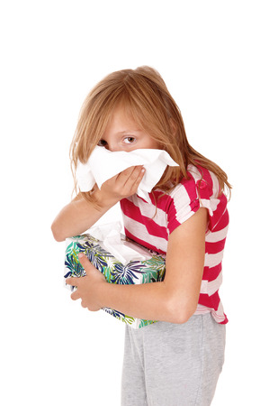 A lovely young blond girl blowing her running nose, holding a tissue boxin her hand, isolated for white background. photo