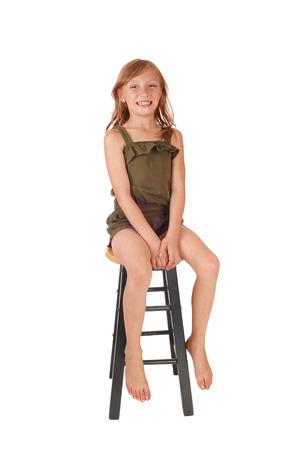 Een jonge glimlachende blond meisje in een olijfgroen jumpsuit zittend in een kale stoel, geïsoleerd op een witte achtergrond.