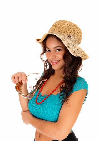 A portrait picture of a teenager girl wearing a turquoise blouse, a straw hatand sunglasses, standing isolated for white background. photo