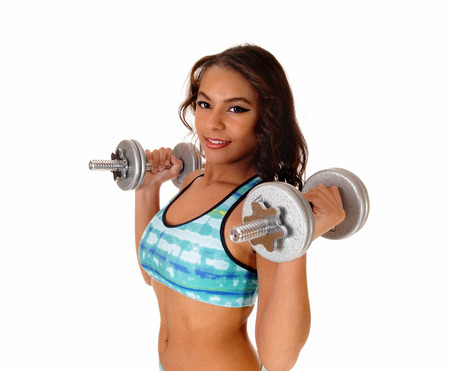 A pretty woman in a turquoise sports bra standing isolated  for white background lifting two dumbbell photo