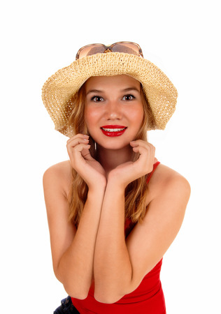 A beautiful blond woman in a red t-shirt, wearing a straw hat, standing isolated for white background. photo