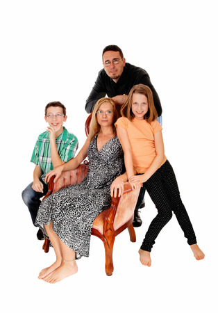 A family group, the mom sitting in a pink armchair and the husband,daughter and son standing, isolate for white background. photo