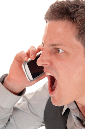 A closeup picture of a young man screaming in his cell phone, with hismouth wide open, isolated for white background. photo