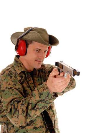 A closeup picture of a soldier in a camouflage uniform pointing a pistol,with ear protection, isolated on white background. photo
