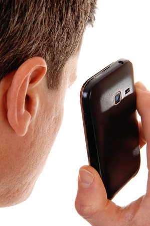 phone: A closeup shoot of a man from the back holding his cell phone on hisear, isolated for white background.