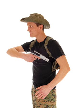 holster: A soldier in camouflage pants, hat and black t-shirt pulling his hand gunout of the holster, isolated on white background.