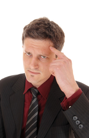 A serious looking businessman in a suit and tie with his finger on hisforehead, isolate on white background. photo
