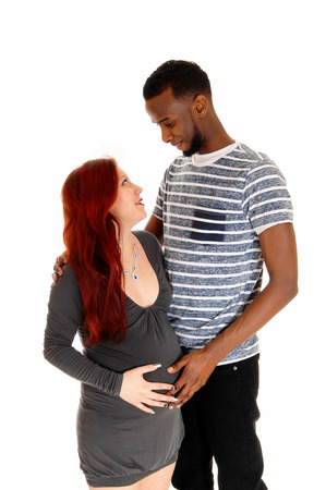 A young pregnant woman in a grey dress and red hear looking up toher man, an African American, isolated for white background. photo