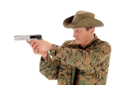 A closeup picture of a soldier in a camouflage uniform pointing a pistol,isolated on white background. photo