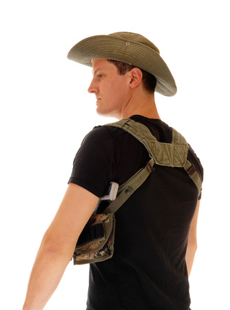 holster: A soldier in a black t-shirt and pistol holster, wearing a hat, standingfrom the back, isolated for white background.