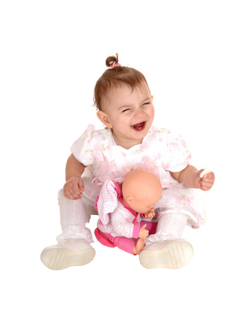 A small baby girl sitting on the floor, laughing and playing with herdolly, isolated for white background. photo
