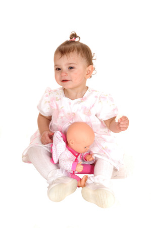 A lovely blond baby girl sitting on the floor holding her biscuits and playingwith her dolly, isolated for white background. photo