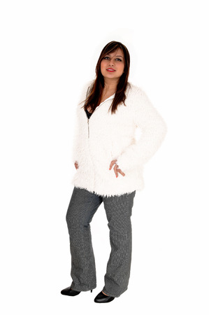 A brunette young woman standing isolated for white background in a whitejacket and grey pants. Stock Photo