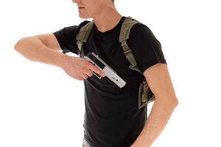 holster: A soldier in black t-shirt, pulling his hand gunout of the holster, isolated on white background.