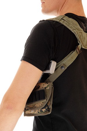 holster: A soldier in black t-shirt with his gun in the holster, an closeup from theback, isolated on white background. Stock Photo