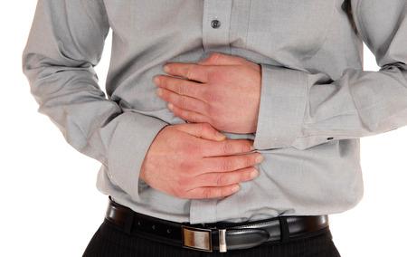 persona triste: Un cuadro del primer del est�mago de un hombre joven sosteniendo sus manos enel est�mago para el dolor pesado, aislado de fondo blanco.