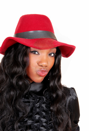A closeup picture of a lovely African American woman in a black blouseand red hat and curly hair blowing a kiss, isolated for white background. photo