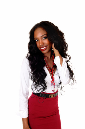 A halve length picture of a black girl in a white blouse and red skirt andlong curly black hair standing isolated for white background.