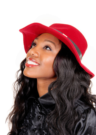 A lovely African American woman in a black blouse and long black curlyhair with a red hat looking up, isolated for white background. photo