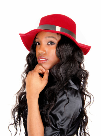 A lovely African American woman in a black blouse and long black curlyhair with a red hat, isolated for white background. photo
