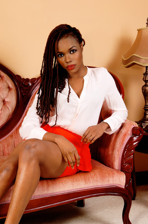 A lovely young African American woman in a red skirt and long braidedhair sitting on a pink antic sofa. photo