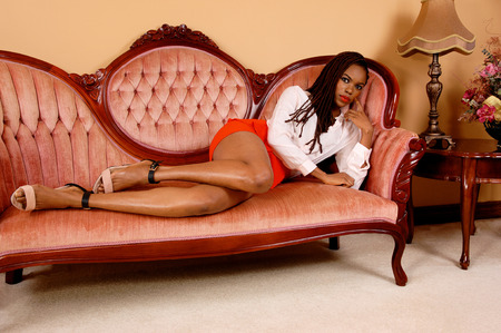 baited: A beautiful young African American woman in a red skirt lying on a pinkantic sofa in the living room. Stock Photo