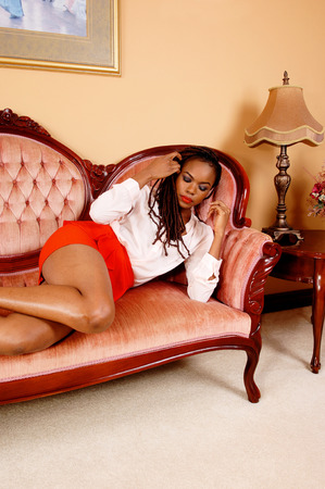 A lovely young African American woman in a red skirt lying on a couch andsleeping in the living room. photo