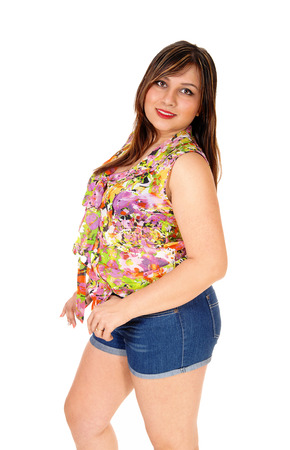 A young pretty woman in jeans shorts standing in profileand looking over her shoulder, isolated for white background. photo