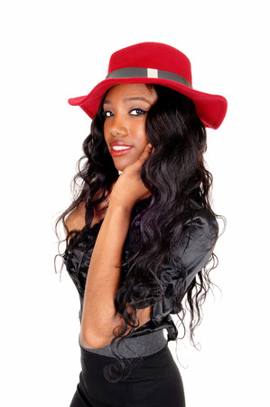 A beautiful African American woman in a black skirt and blouse with ared hat standing in profile, isolated for white background. photo