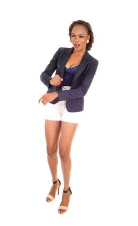 A slim young African American woman in white shorts and a grey jacketand high heels, standing isolated for white background.