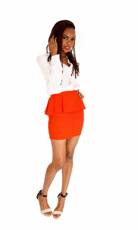 A lovely young and slim African American woman standing in a red skirtwith her long breaded brown hair, isolated for white background. Stock Photo